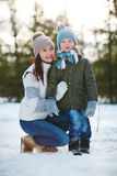 Winter portrait of mother and son. Portrait of rosy-cheeked little boy with snow on his outwear and his attractive young mother sitting on haunches and embracing Royalty Free Stock Photo