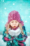 Winter portrait of a pretty little girl. Colorful winter portrait of a pretty little girl blowing snow stock photo