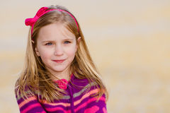 Winter portrait of pretty young girl. Winter or early spring portrait of pretty young girl child wearing knit poncho at park while showing off temporary peace Royalty Free Stock Images