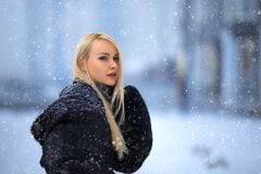 Beautiful blonde girl portrait under the snow royalty free stock images