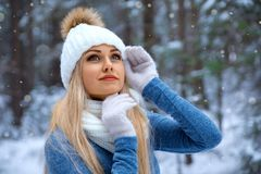 Beautiful blonde girl in red hat and gloves. Winter portrait of smiling beautiful blonde girl in white hat and gloves under the snow - closeup beauty photo royalty free stock image