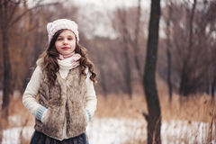 Winter portrait of smiling child girl on the walk in snowy forest Royalty Free Stock Images