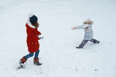 Winter portrait of two girls having fun, children playing with s stock images