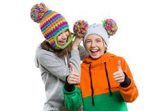 Winter portrait of two happy smiling pretty girls in knitted hats having fun, isolated on white background, people, youth and frie. Ndship concept Royalty Free Stock Image