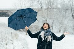 A cute young girl holds umbrellas in the hands of the winter season Royalty Free Stock Photography