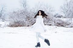 Winter portrait of young beautiful brunette woman wearing ear mu Stock Photography