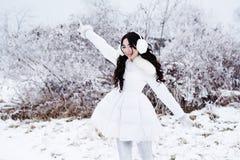 Winter portrait of young beautiful brunette woman wearing ear mu Royalty Free Stock Photos