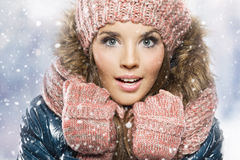Winter portrait of young beautiful brunette woman wearing knitted snood covered in snow. royalty free stock photo