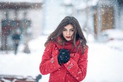 Winter portrait of young beautiful brunette woman wearing knitted snood and red coat covered in snow. Snowing winter beauty fashio royalty free stock photo
