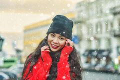 Winter portrait of a young beautiful girl on the streets of a European city. Model wearing coat, scarf, hat royalty free stock photos