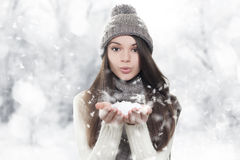 Winter portrait. Young, beautiful woman blowing snow. Toward camera on winter background Stock Image