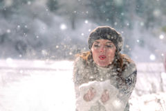 Winter portrait. Young, beautiful woman blowing snow toward camera on winter background. Winter portrait. Young beautiful woman in a beret and vest blowing snow Royalty Free Stock Photo