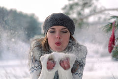 Winter portrait. Young, beautiful woman blowing snow toward camera on winter background. Winter portrait. Young beautiful woman in a beret and vest blowing snow Royalty Free Stock Images