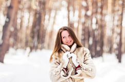 Winter portrait of young beautiful woman wearing fur coat. Snow winter beauty fashion concept. Stock Photos