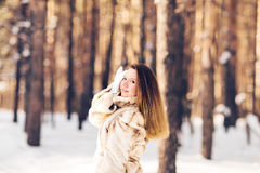 Winter portrait of young beautiful woman wearing fur coat. Snow winter beauty fashion concept. Royalty Free Stock Images