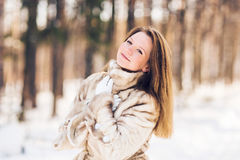 Winter portrait of young beautiful woman wearing fur coat. Snow winter beauty fashion concept. Royalty Free Stock Photos