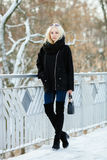 Winter portrait: young blonde woman dressed in a warm woolen jacket blue jeans long boots posing outside in a snowy city park royalty free stock images