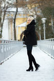 Winter portrait: young blonde woman dressed in a warm woolen jacket blue jeans long boots posing outside in a snowy city park stock photos