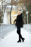Winter portrait: young blonde woman dressed in a warm woolen jacket blue jeans long boots posing outside in a snowy city park stock photography