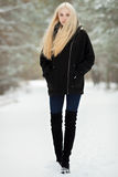 Winter portrait: young blonde woman dressed in a warm woolen jacket blue jeans long boots posing outside in a snowy park royalty free stock images
