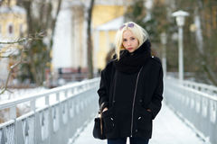 Winter portrait: young blonde woman dressed in a warm woolen jacket posing outside in a snowy city park royalty free stock photos