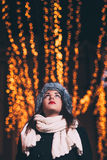 Winter portrait of young fashion woman. Looking at New Year lighting Royalty Free Stock Photography