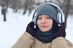 Winter portrait of young girl with headphones Stock Photos
