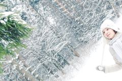 Winter portrait of a young girl standing near spruce.  Stock Photo