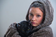 Winter portrait of young kind woman holding big black cat Royalty Free Stock Photography