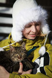 Winter portrait of young kind woman holding big cat Stock Photos