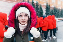 Winter portrait of a young woman against the backdrop of people in red jackets royalty free stock images