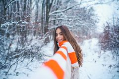 Winter portrait of young woman in the winter snowy scenery. Portrait of a young woman in snow trying to warm herself. royalty free stock photo