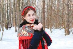 Winter portreit lächelndes Mädchen mit dem schönen Haar auf ihrem Kopf in der russischen Volksart in den roten Schalen Stockbild