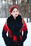 Winter portreit lächelndes Mädchen mit dem schönen Haar auf ihrem Kopf in der russischen Volksart in den roten Schalen Stockfotos
