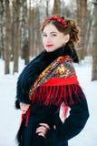 Winter portreit lächelndes Mädchen mit dem schönen Haar auf ihrem Kopf in der russischen Volksart in den roten Schalen stockfoto
