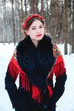 Winter portreit smiling girl with beautiful hair on her head in Russian folk style in red shawls stock photos
