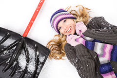 Winter: Pretty Woman Lying Next to Snow Shovel Royalty Free Stock Photos