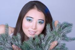Winter protrait of Asian girl by Christmas tree Royalty Free Stock Images
