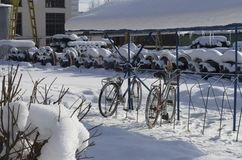 Winter provincial landscape with old parked bicycles. And a warehouse of diesel wheeled axles covered with snow stock photography