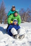 Winter race. Two teens pushing their friend sitting on a snowboarder Stock Images