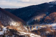 Winter rail road transportation in mountains. Freight train with colorful carriage on the old viaduct stock photos