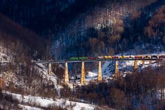 Winter rail road transportation in mountains. Freight train with colorful carriage on the old viaduct royalty free stock images