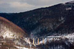 Winter rail road transportation in mountains. Old viaduct between the hills royalty free stock image