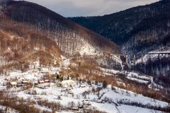 Winter rail road transportation in mountains. Station and village on hill and viaduct in the distance stock photos