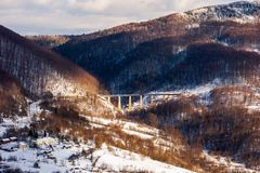 Winter rail road transportation in mountains. Station and village on hill and viaduct in the distance. beautiful scenery in dappled light royalty free stock photo