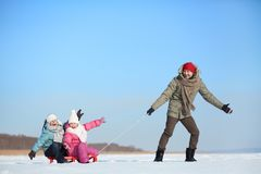 Winter recreation. Happy kids sitting on sledge while their father pulling them Royalty Free Stock Images