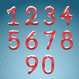Winter red numbers set with snow caps. Frozen New year digits wi. Th snowflakes on it kit. Icicles numbers on dark snowy background Stock Photos