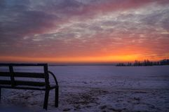 The red color of the sunset. Winter red sunset. Bench at sunset. Stock Images