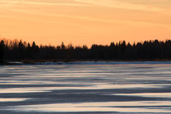 Winter reflections. Mellow dusk in winter with the last rays of sun reflecting on a frozen lake Stock Image