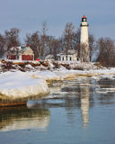 Winter reflections Point Aux Barques Lighthouse. Beautiful lighthouse reflections and melting ice, Wintertime sunrise at Point Aux Barques Lighthouse. Michigan Royalty Free Stock Images